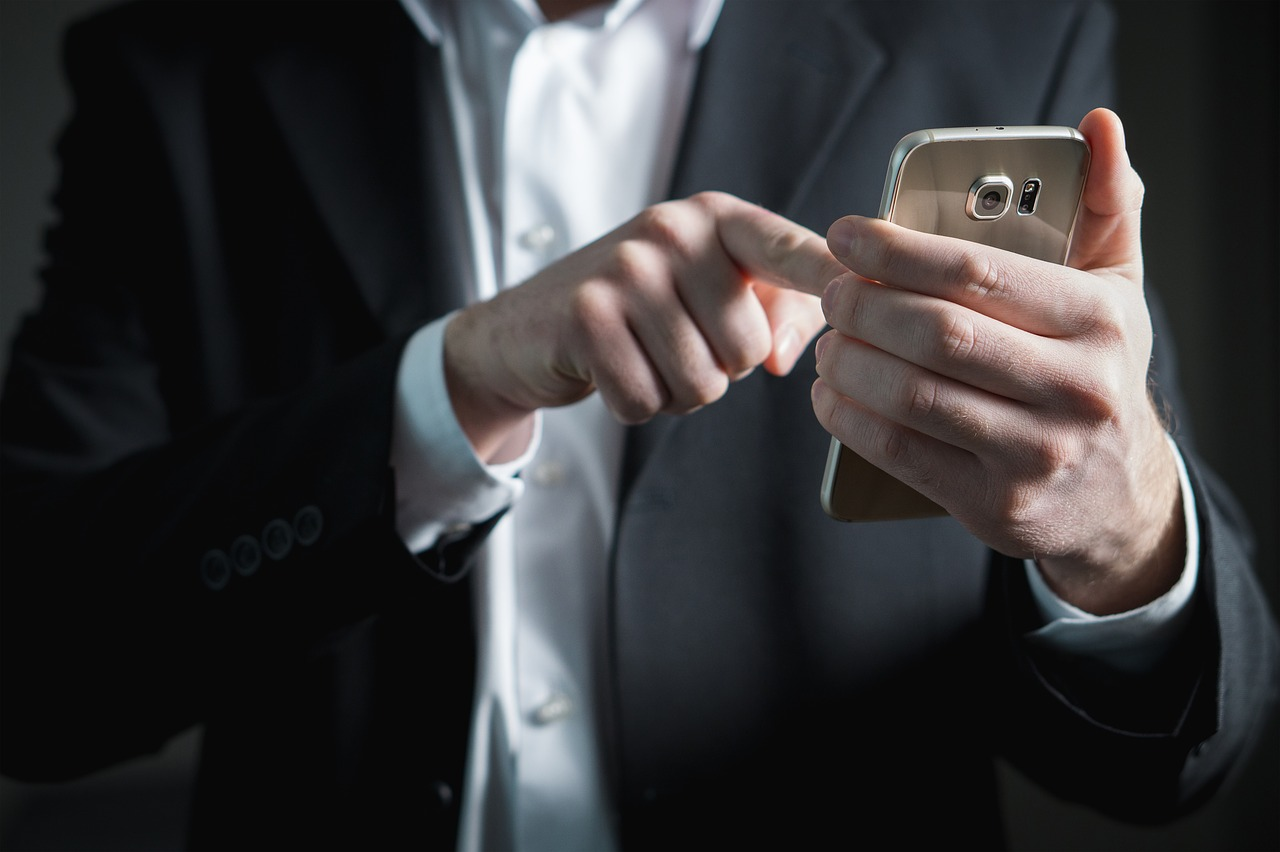 man holding and scrolling his phone