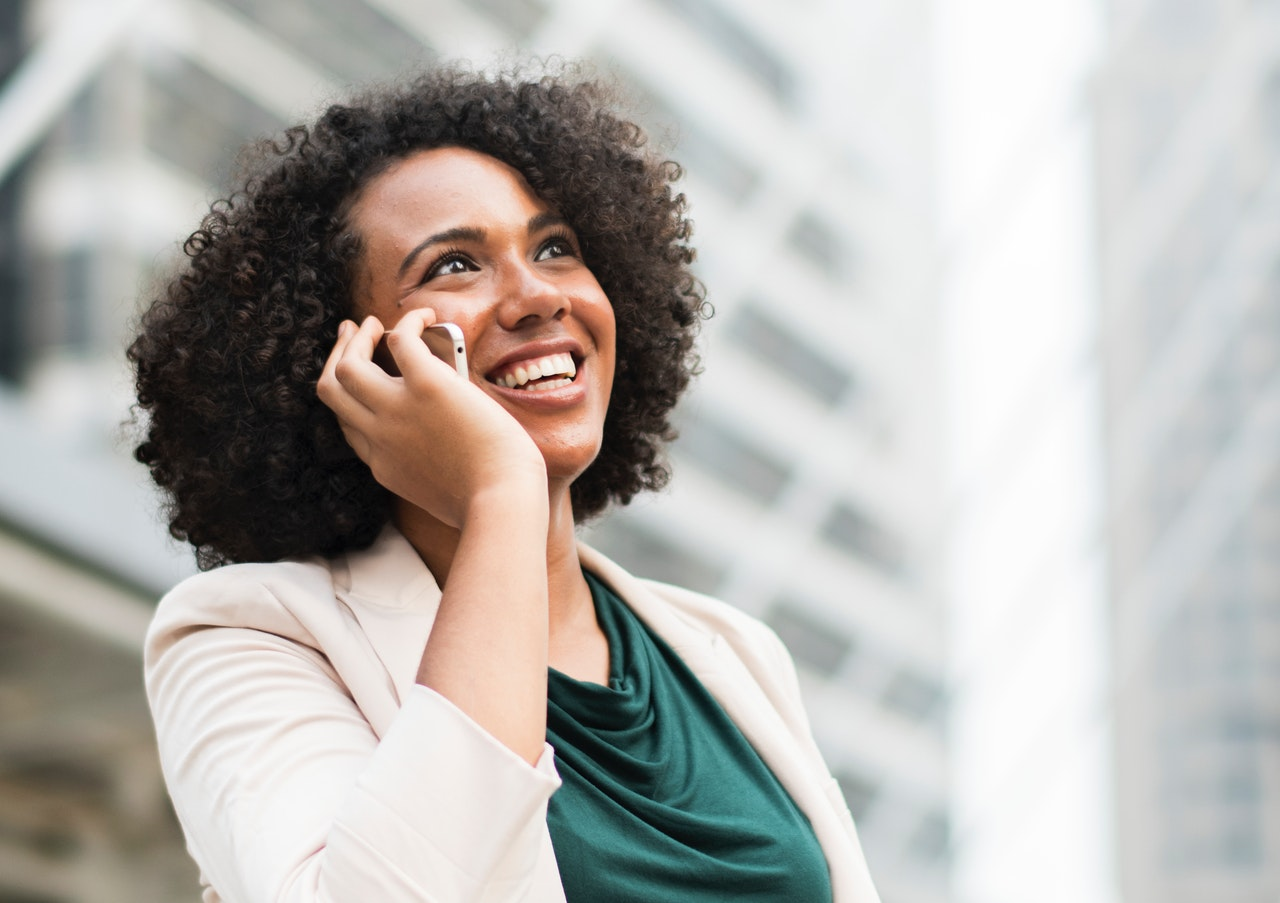 woman smiling while holding a phone