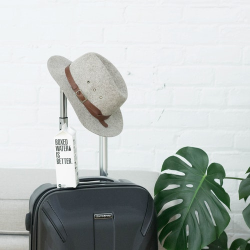 A hat and Boxed Water carton sit on a suitcase