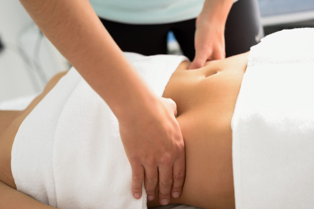 hands massaging female abdomen therapist applying pressure belly