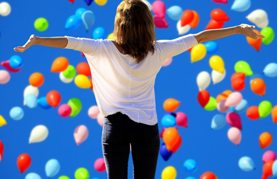 woman with open arms and colorful falling ballons