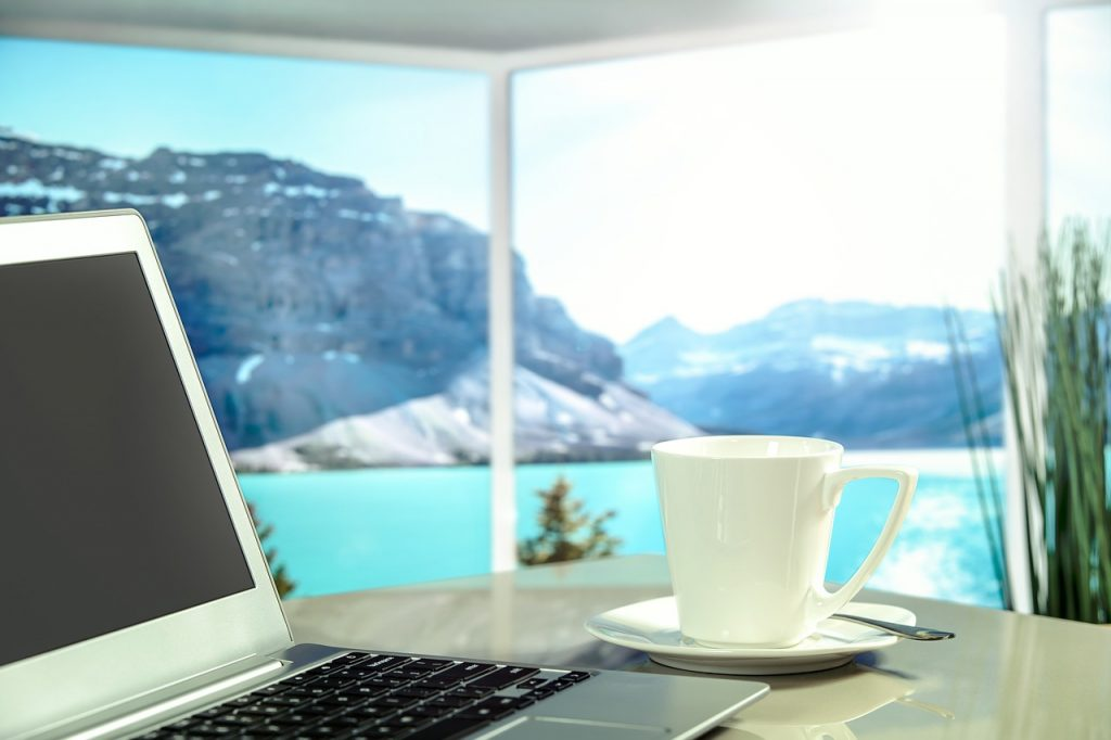 laptop and coffee mug by an ocean view